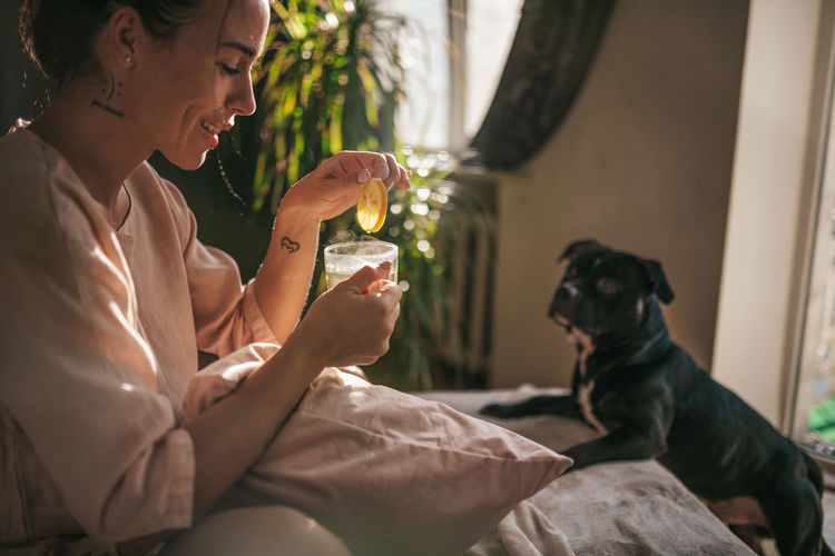 Woman holding dog sitting at home