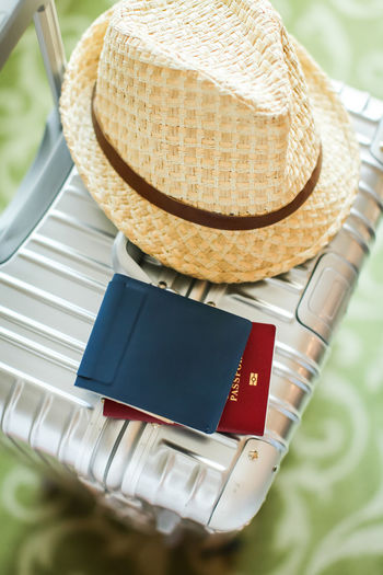 High angle view of hat and passport on luggage