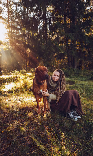 Land Tree Plant Real People Nature Leisure Activity Forest Domestic Animals Domestic Togetherness Young Adult Mammal Field Two People Pets Young Women Canine Dog Animal Themes Positive Emotion Outdoors WoodLand