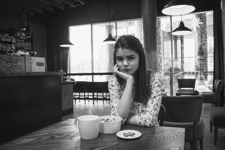 Portrait Of Young Woman Sitting In Restaurant