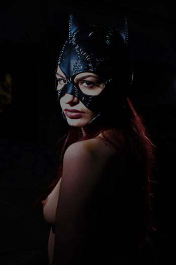 Portrait of shirtless woman in eye mask standing by black background