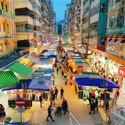 High angle view of people at night street market in city