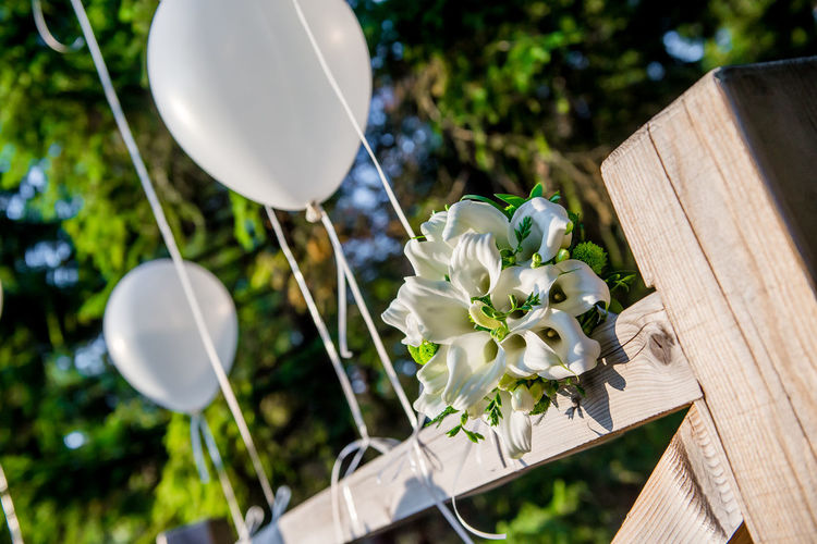Calla Lily Bridal Bouquet With Balloons Arranging On Wooden Fence