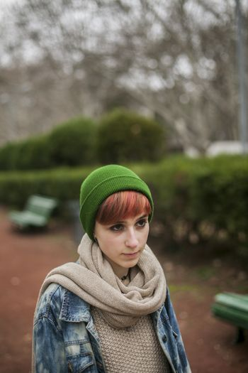 Young woman looking away while standing in park during winter