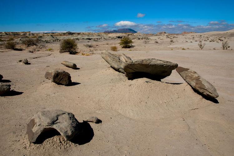 Rocks on sand against sky