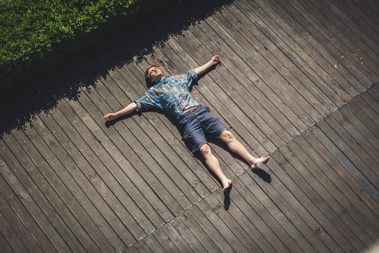 High Angle View Of Carefree Man With Arms Outstretched Lying On Boardwalk
