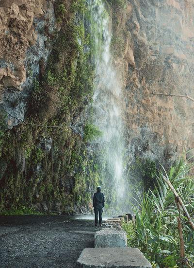Rear view of man looking at waterfall