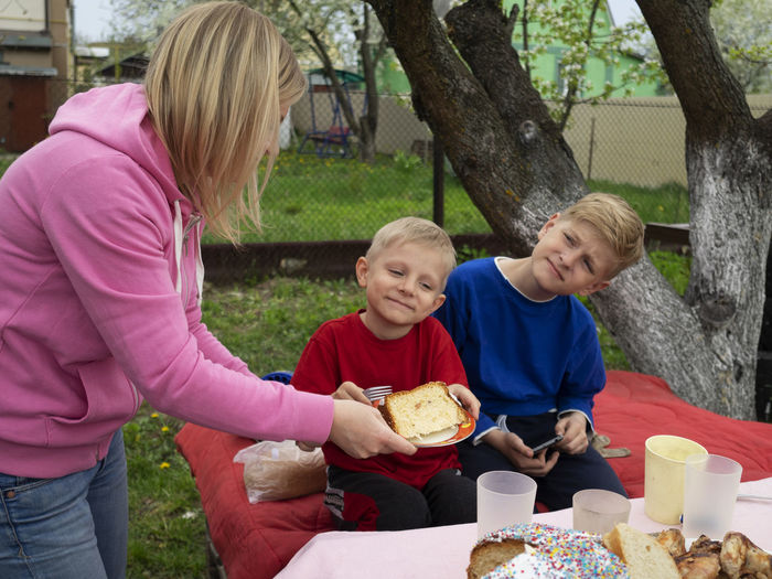 Woman serving bread to sons at lawn