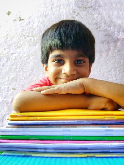 Smiling boy with books Cute Smile  Asian  Window Light Sunlight Happy Child  Boy Books Cheerful Smiling Face Looking At Camera Kid Confidence  Happiness Education Cute Indian Child Childhood Facial Expression Portrait Children Knowledge Pride Arms Crossed Elementary Student Preschooler