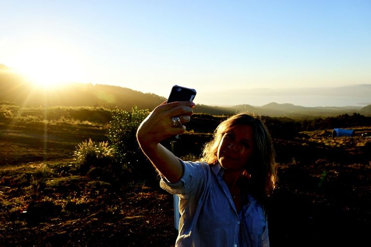 Woman taking selfie through mobile phone while standing on field