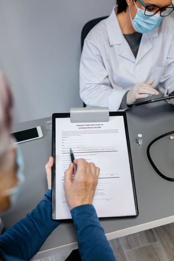 Midsection of man having discussion with doctor at clinic