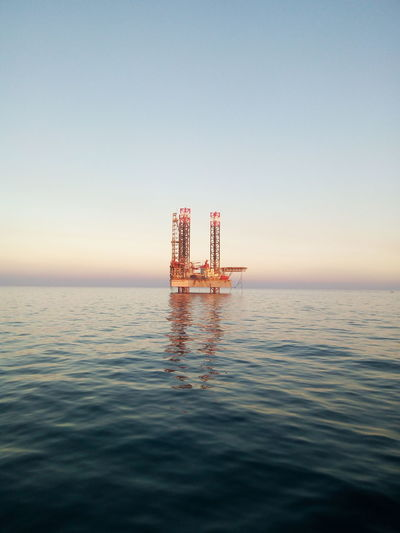 Offshore platform in sea against clear sky during sunset