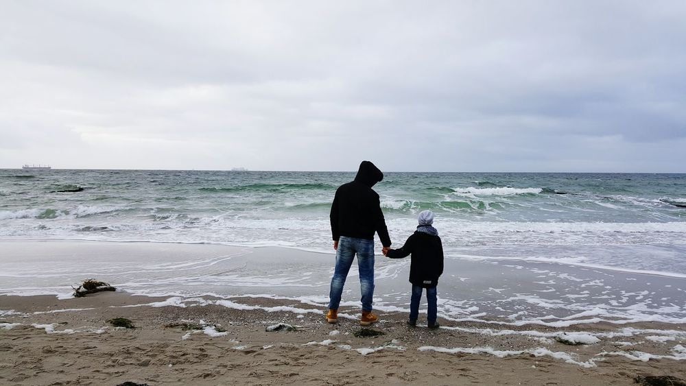 Beach Sea Two People Horizon Over Water Travel Destinations Sand Rear View Outdoors Wave Togetherness Vacations People Cloud - Sky Nature Adult Water Sky Day Fatherhood Moments Father And Son