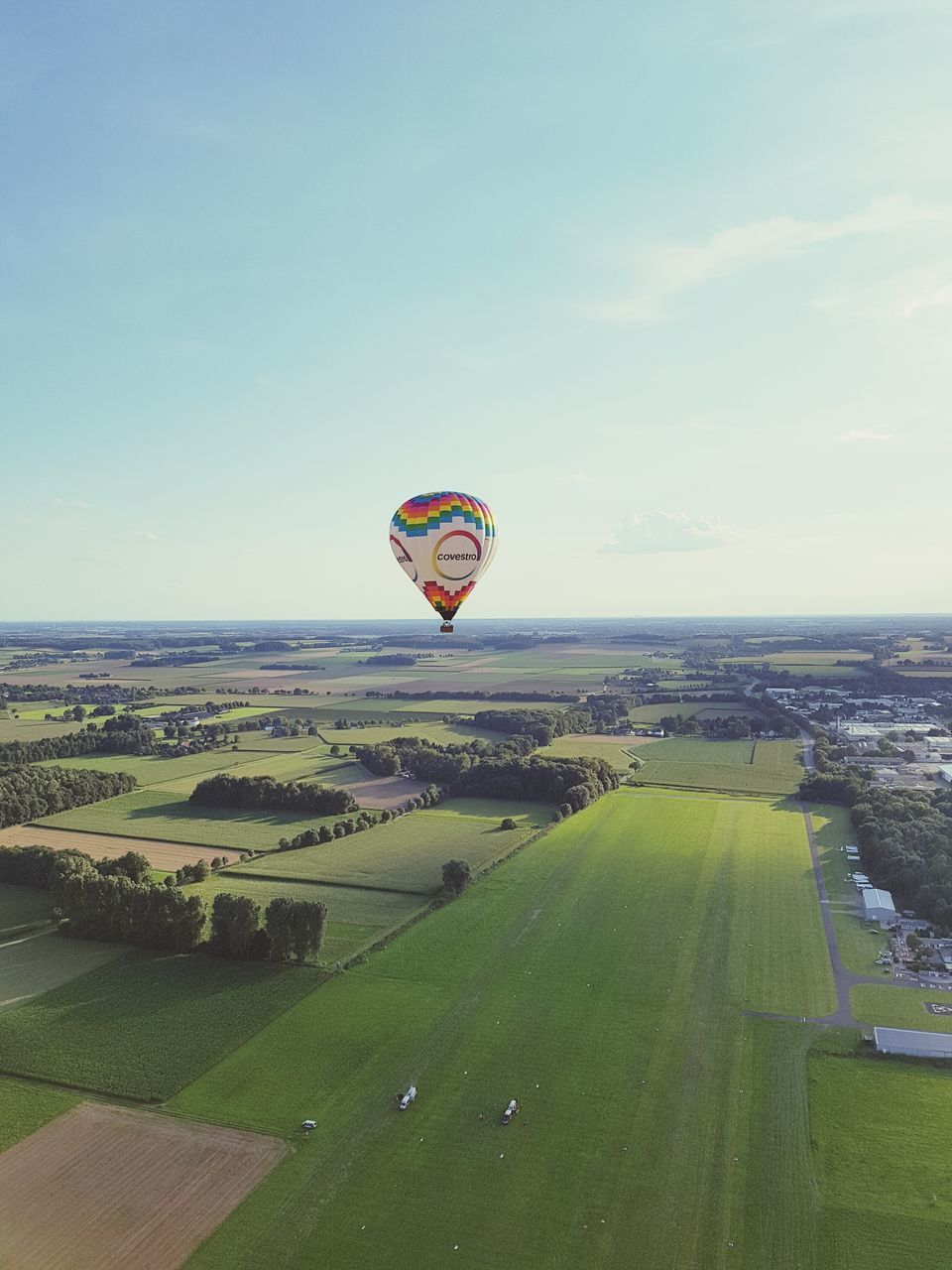 mid-air, flying, parachute, landscape, adventure, sky, transportation, extreme sports, sport, hot air balloon, day, outdoors, field, grass, leisure activity, scenics, nature, tree, architecture, building exterior, no people, beauty in nature, paragliding, ballooning festival