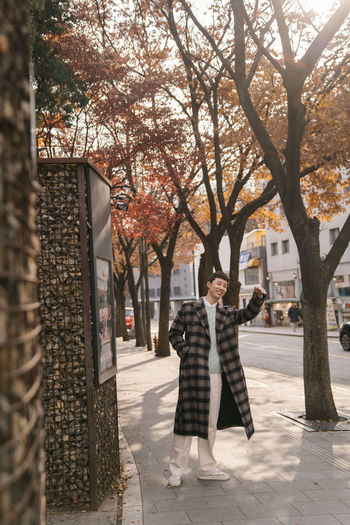 Woman walking on footpath by street in city during autumn