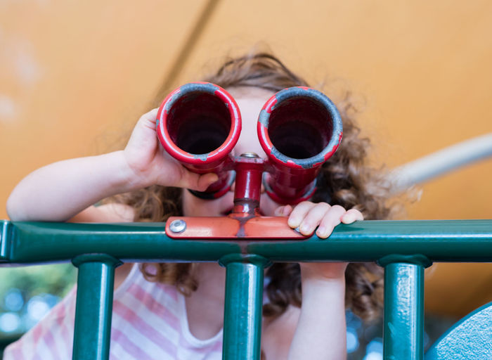 Close-Up Of Girl Looking Through Binoculars