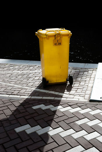 Yellow garbage can on footpath during sunny day