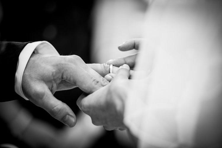 Woman wearing ring to groom during wedding
