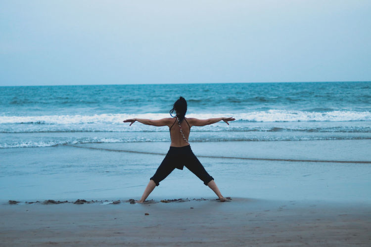 Rear view of woman with arms outstretched standing at beach against clear sky
