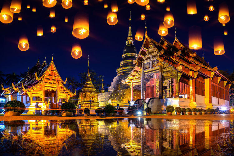 Yee peng festival and sky lanterns at Wat Phra Singh temple at night in Chiang mai, Thailand. Illuminated Built Structure Architecture Building Exterior Night Building Belief Religion Place Of Worship Reflection Spirituality Travel Destinations Lighting Equipment Water City Tourism Travel