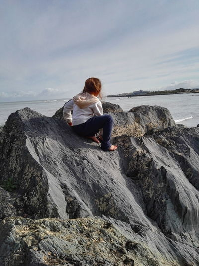 Rear view of girl on rock formation by sea against cloudy sky