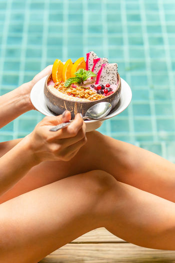 Woman holding smoothie bowl with mixed fruits and granola by swimming pool
