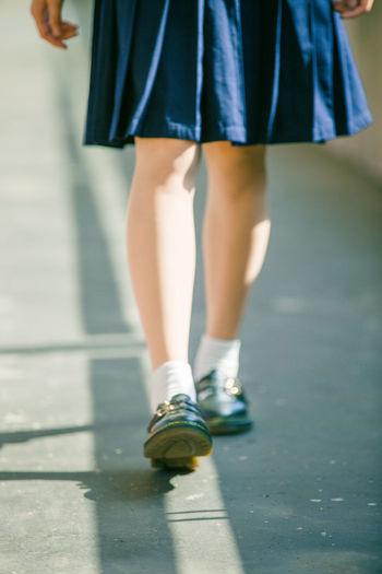 Low section of schoolgirl walking in corridor