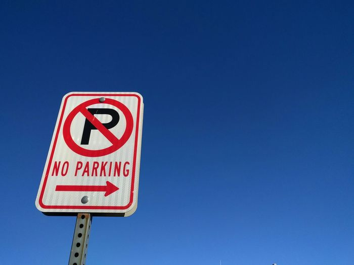 Low angle view of no parking sign against clear sky