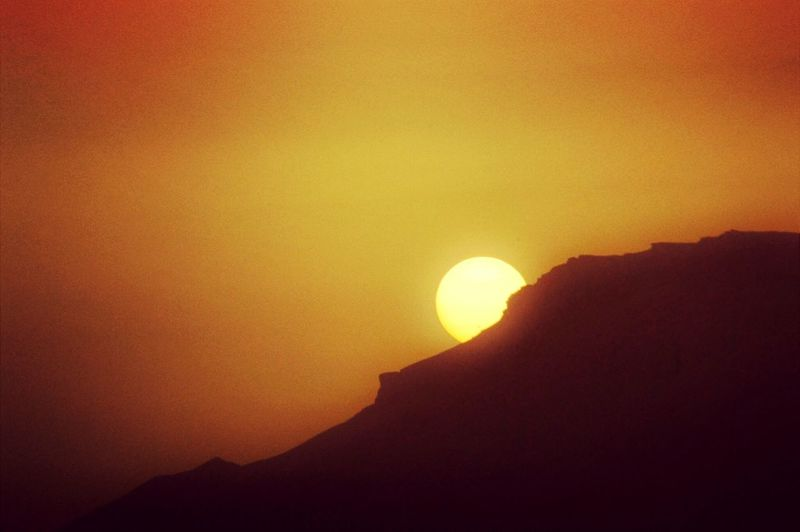 Low angle view of silhouette mountain against orange sky during sunset