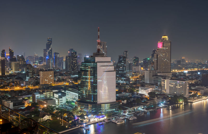 Aerial view of colorful lighting from building along chaophraya river on night, thailand