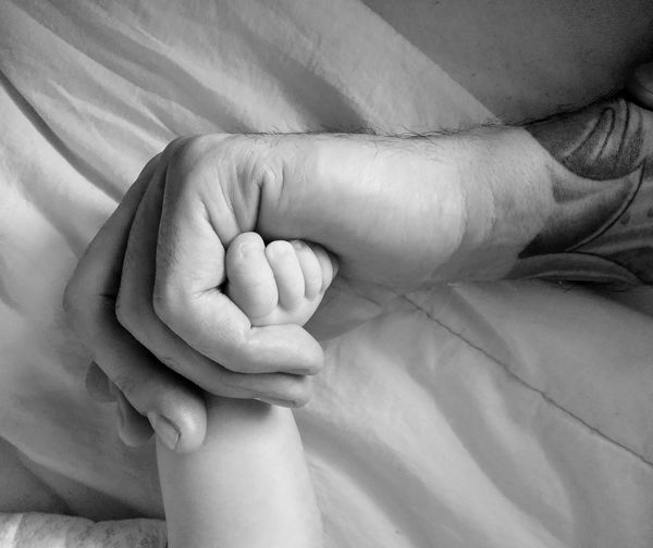 Close-up of cropped hand holding child leg on bed at home