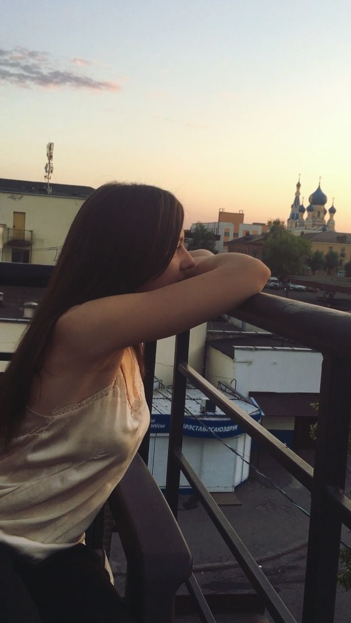 sky, one person, architecture, building exterior, built structure, nature, city, railing, side view, sunset, three quarter length, leisure activity, young adult, waist up, women, adult, hairstyle, long hair, outdoors, cityscape, contemplation