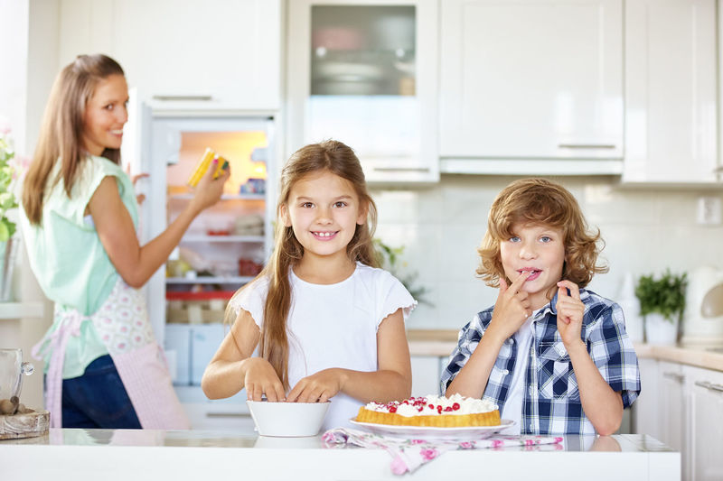 Mother Looking At Children Making Cake In Kitchen At Home