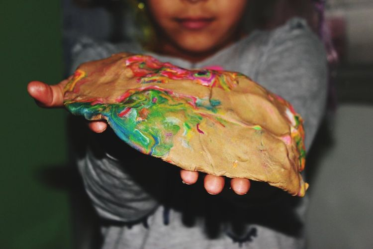 Midsection of girl holding dough with paint