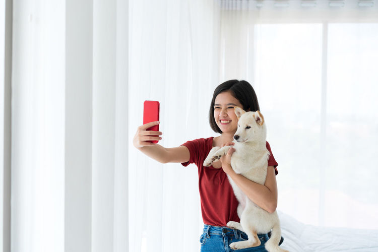 Cheerful woman holding dog taking selfie at home