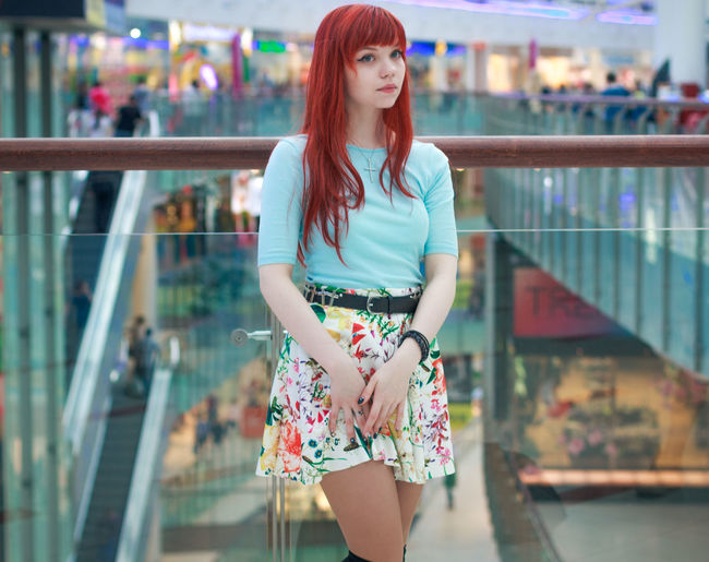 Beautiful woman with redhead looking away while standing by railing at shopping mall