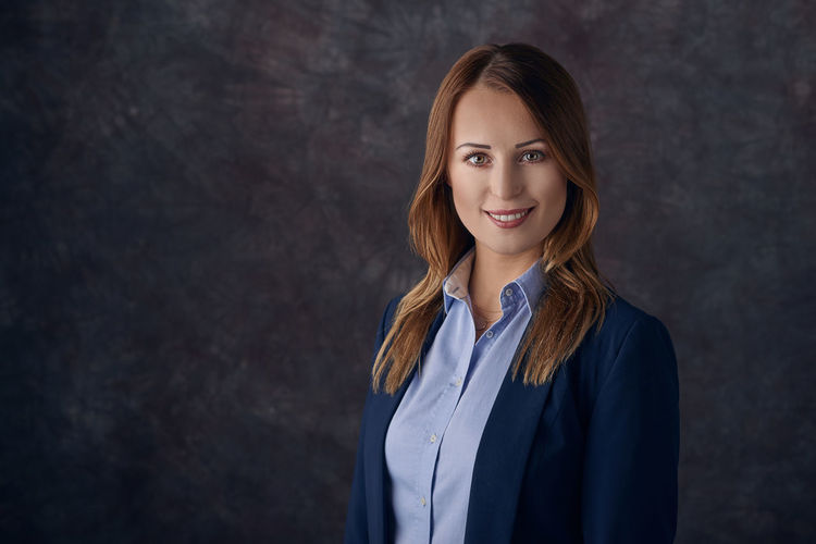 Portrait of young businesswoman standing against wall