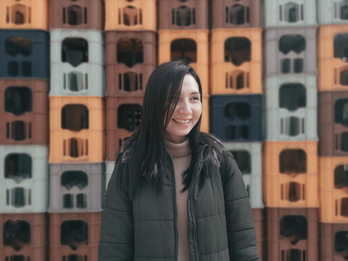 Smiling Woman Standing Against Stacked Containers