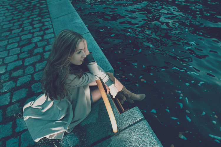 High angle view of woman sitting by canal