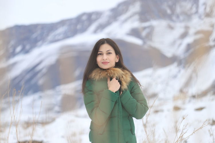 Portrait of young woman standing on snow covered landscape