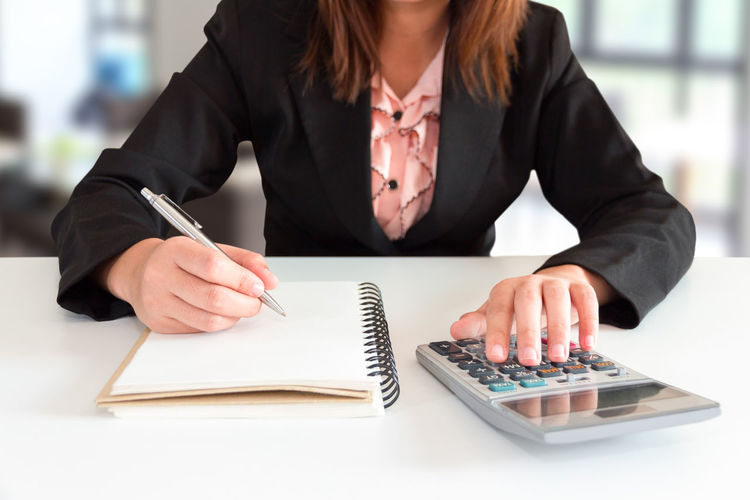 Midsection o businesswoman writing on book in office
