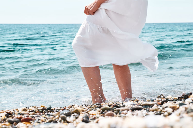 Happy woman in white dress walks in the pebble beach with crystal sea and blue sky.