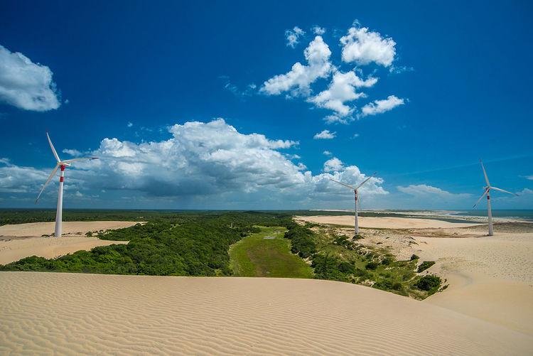Wind turbines on sand dunes against blue sky