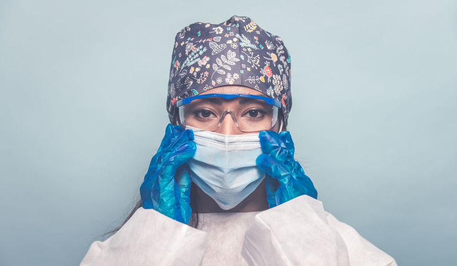 Portrait of doctor wearing mask against colored background