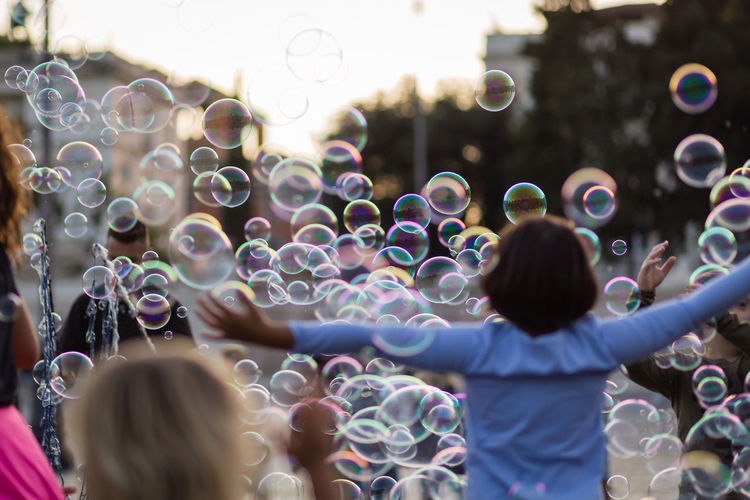 Cheerful kids playing amidst bubbles on road