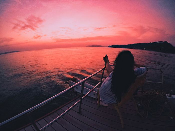 Woman relaxing by sea at sunset