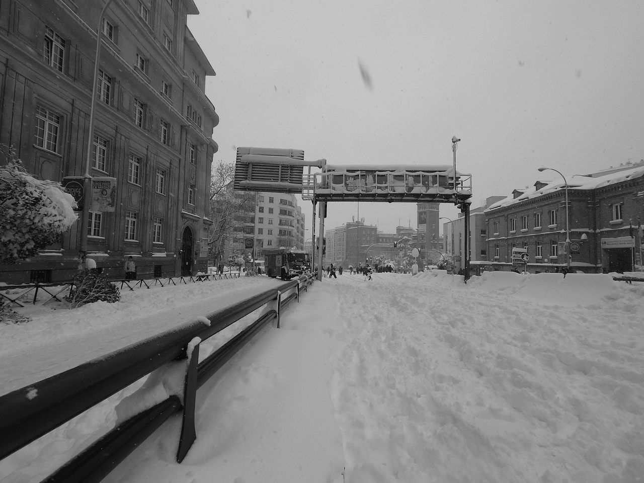 SNOW COVERED STREET BY BUILDINGS AGAINST SKY