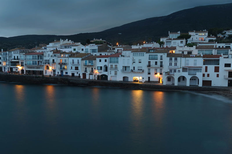 Cadaques by sea against cloudy sky at dusk
