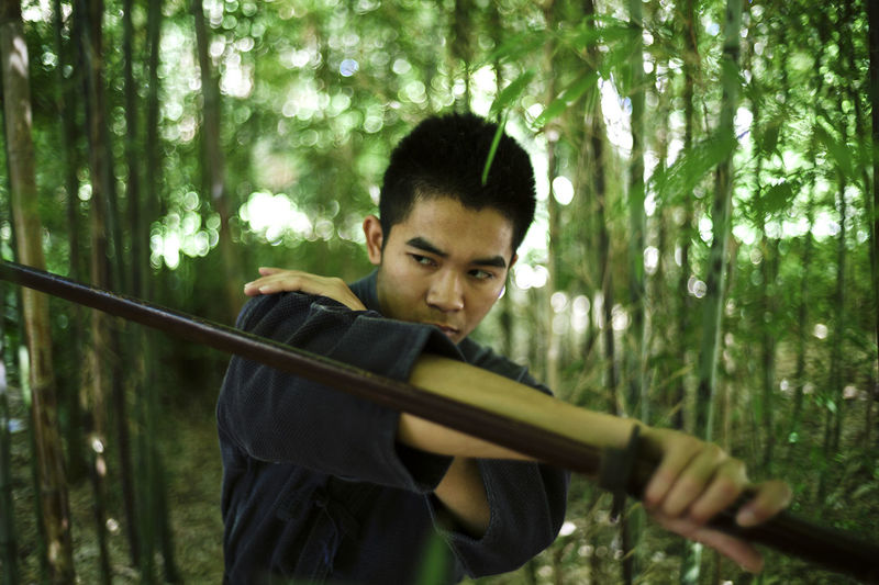 The modern samurai. Bamboo - Plant Close-up Concentration Day Focus On Foreground Forest Front View Headshot Holding Leisure Activity Lifestyles Looking At Camera Nature One Person Outdoors People Portrait Real People Skill  Standing Tree Weapon Young Adult Young Men Young Women