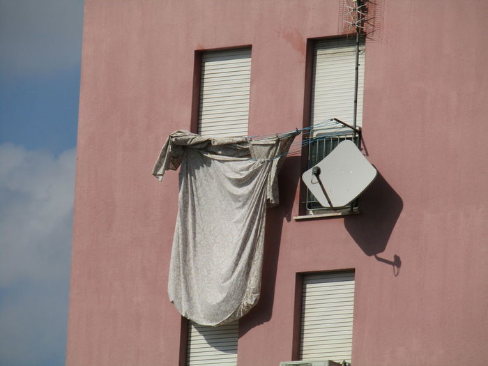 Tv antenna and sheets on the facade of a building in a minimal photo